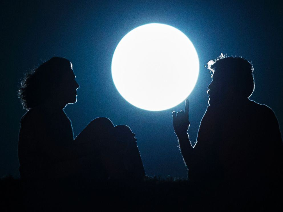 A couple talk as they sit against the perigee moon, also known as a supermoon, in Madrid, Aug. 10, 2014. Andres Kudacki/AP Photo