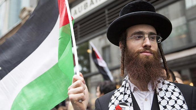 An ultra-Orthodox Jew holds a Palestinian flag during a protest against Israel's air strikes in Gaza in London July 11, 2014. (Reuters / Neil Hall)