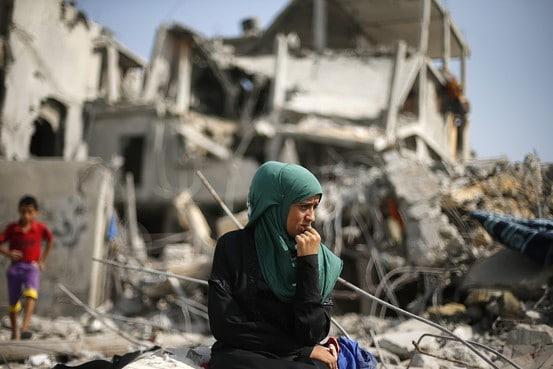 A Palestinian woman sits on the remains of her destroyed house Tuesday after returning to Beit Hanoun town, which witnesses said was heavily hit by shelling and air strikes during the Israeli offensive. Reuters