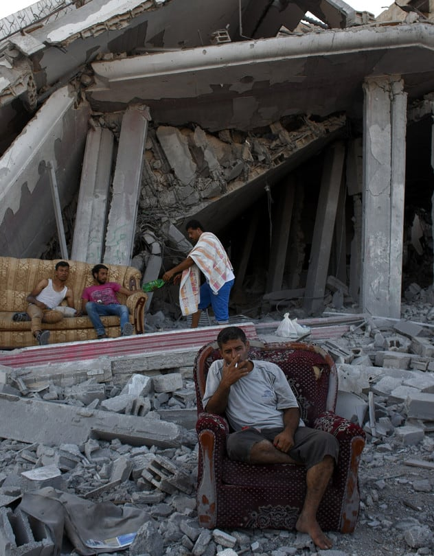 Displaced Palestinians sit amid the rubble of destroyed homes in Gaza on Tuesday. Heidi Levine/Sipa Press