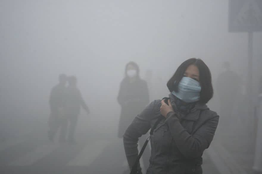 A woman wearing a mask walk through a street covered by dense smog in Harbin, northern China. Credit: Kyodo News