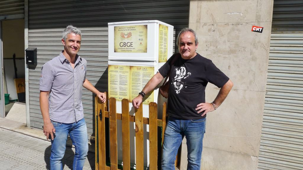 """The mayor and a volunteer in front of the """"Solidarity Fridge"""" installed to feed the hungry.  Credit: NPR"""