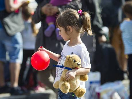A little girl with a balloon and a teddy bear. Credit: Independent UK