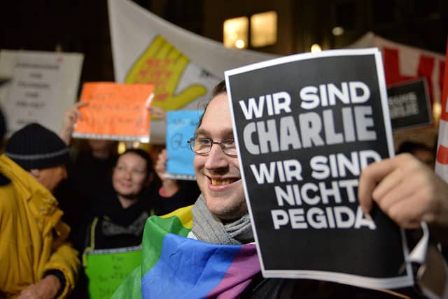 """An anti-fascist protester holds a sign referring to French victims of terrorism, which says: """"We are Charlie. We are not Pediga [a German far-right movement]."""" Credit: CC Flickr, Bündnis 90"""