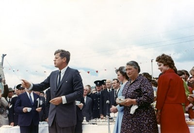 ST-C232-1-63 27 June 1963 President Kennedy's trip to Ireland. The President greets relatives at a tea held at the home of Mrs. Mary Ryan, the President's second cousin, in Dunganstown, Ireland, the President's ancestral homestead. President Kennedy, Mrs. Mary Ryan (flowered dress), Mrs. Josie Ryan (light blue dress), guests, others. Photograph by Cecil Stoughton, White House, in the John F. Kennedy Presidential Library and Museum, Boston. (Wikimedia)