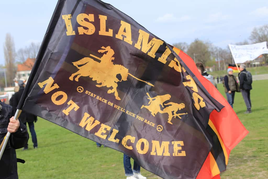 "A flag of German far-right movement Pediga with the message ""Islamists not welcome"". Credit: CC, Flickr, metropolico.org"