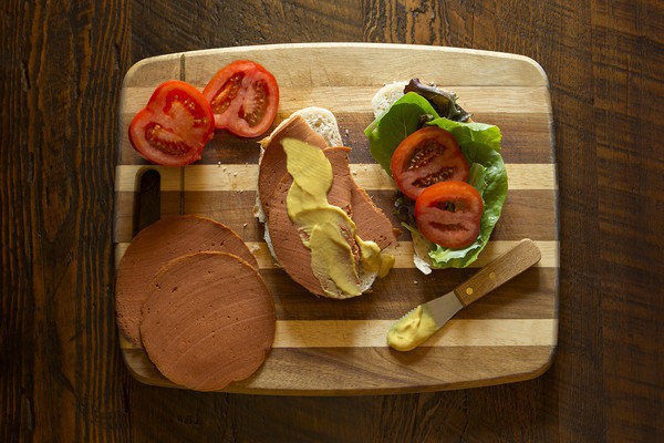 """A meatless bologna deli sandwich, """"made without the mystery."""" Credit: The Herbivorous Butcher"""