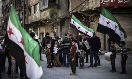 epa05205914 Syrians wave their national flag during a protest against the airstrikes which broke the Russian-US brokered ceasefire a day before, the rebel-held city of Douma, 10 km north-east of Damascus, Syria, 11 March 2016. The ceasefire agreement enters its third week today.  EPA/MOHAMMED BADRA