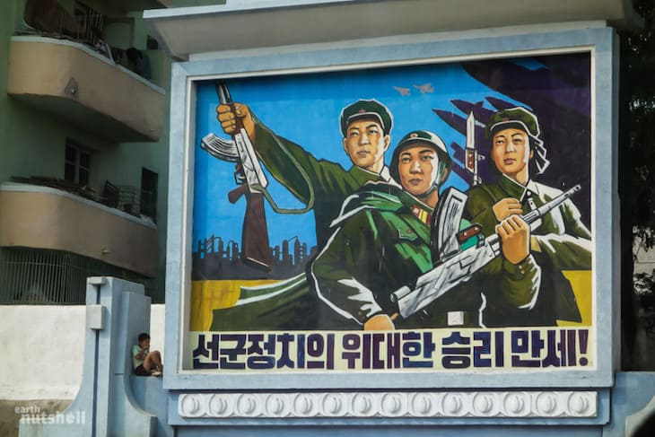 60-a-young-boy-sits-innocently-within-a-giant-militaristic-propaganda-mural-in-the-city-of-haeju