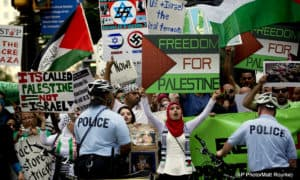 "Protesters demonstrate in opposition of the ongoing Israeli military operation on the Gaza strip, in Friday, July 18, 2014, in Philadelphia. Israeli troops pushed into Gaza on Friday in a ground offensive that officials said could last up to two weeks as the prime minister ordered the military to prepare for a ""significantly"" wider campaign."